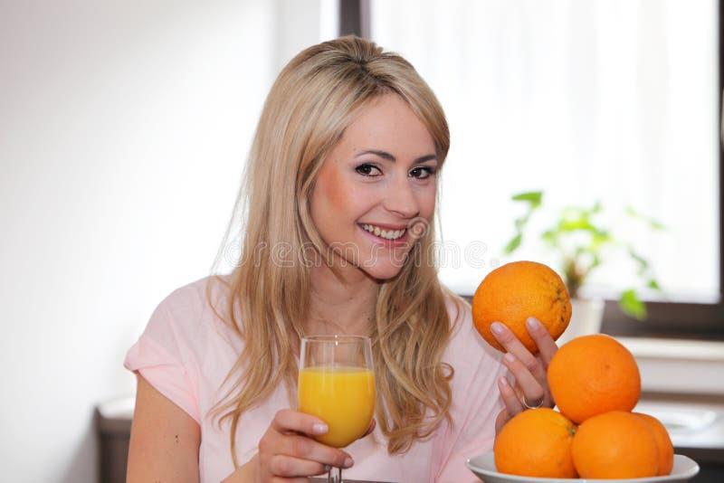 Lycklig kvinna med apelsiner och fruktsaft