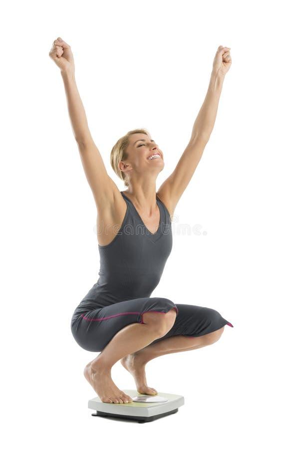 Lycklig kvinna med armar lyftt huka sig ned på viktskala arkivfoton