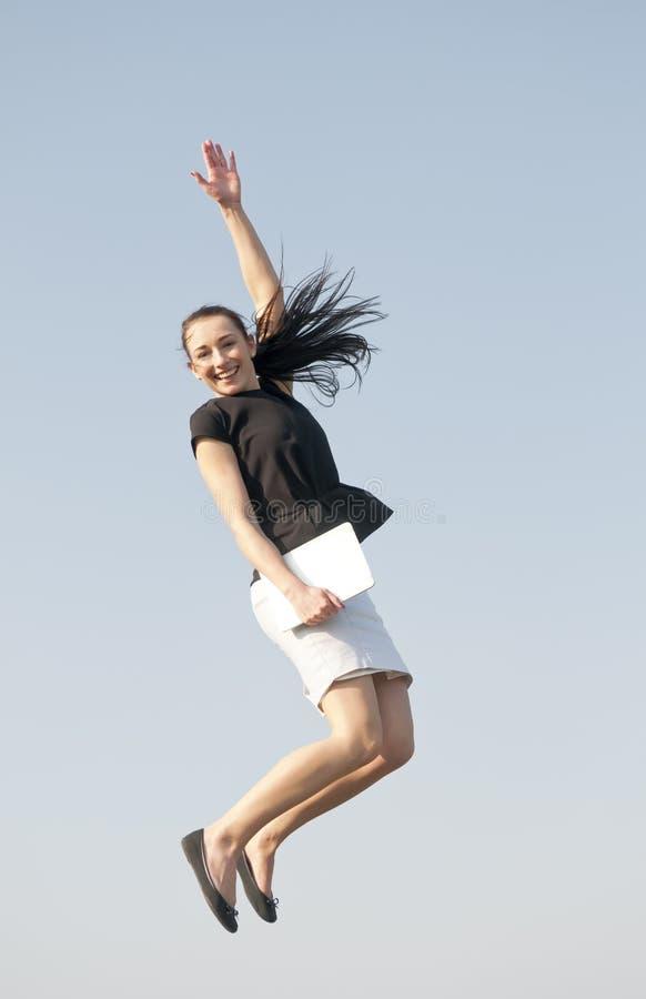 Lycklig kvinna med att hoppa för minnestavlaPC arkivfoto