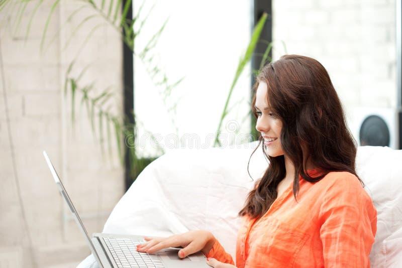 Lycklig kvinna med bärbar datordatoren arkivbild