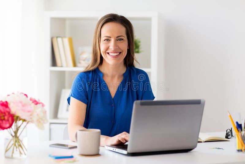 Lycklig kvinna med bärbara datorn som hemma arbetar, eller kontoret arkivbild