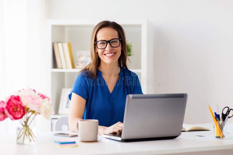Lycklig kvinna med bärbara datorn som hemma arbetar, eller kontoret royaltyfri fotografi