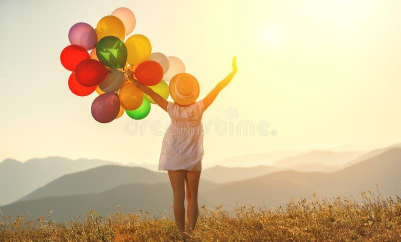 Lycklig kvinna med ballonger på solnedgången i sommar royaltyfria bilder