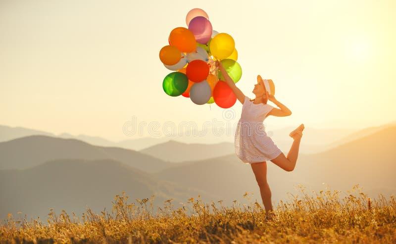 Lycklig kvinna med ballonger på solnedgången i sommar fotografering för bildbyråer