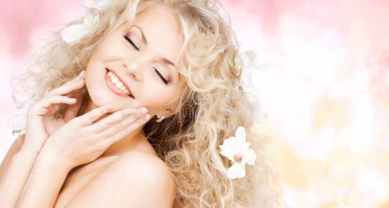 Lycklig kvinna med blommor i hår royaltyfri bild