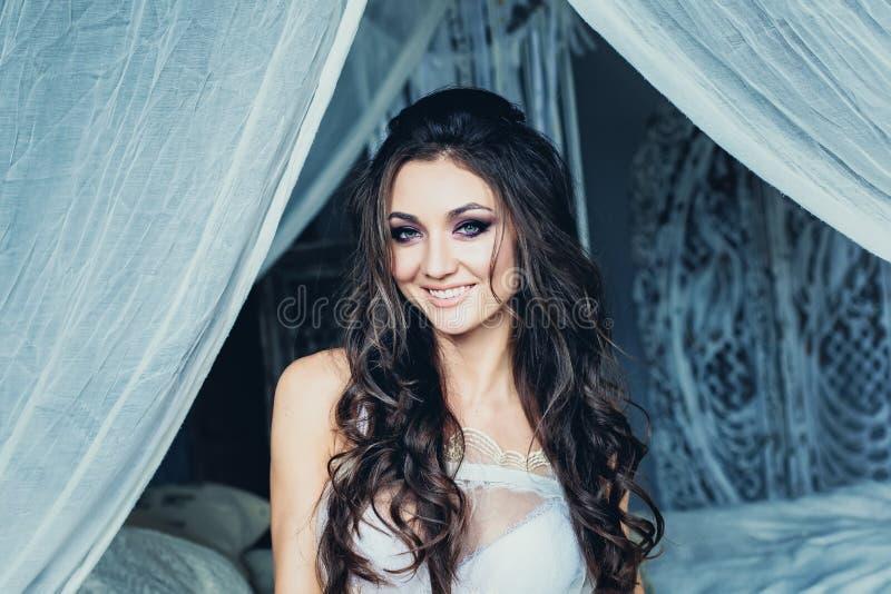 Lycklig kvinna med bröllopfrisyren och brud- makeup royaltyfri bild