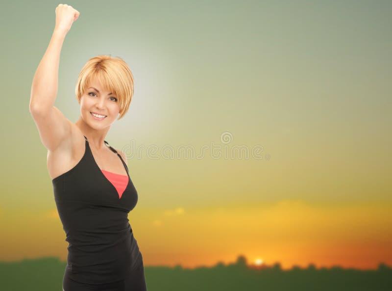 Lycklig kvinna med den lyftta handen över solnedgånghorisont royaltyfri foto