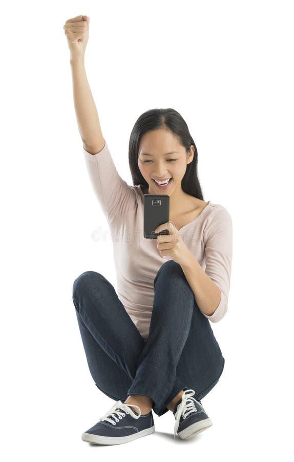 Lycklig kvinna med den lyftta handen genom att använda den smarta telefonen arkivbild