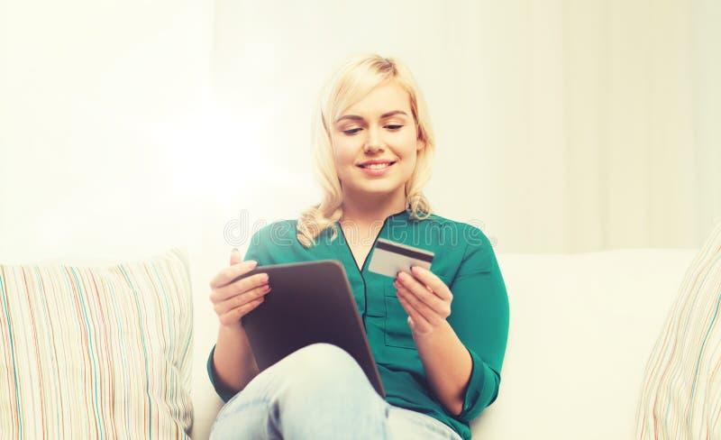 Lycklig kvinna med den tabletPC och kreditkorten royaltyfri fotografi