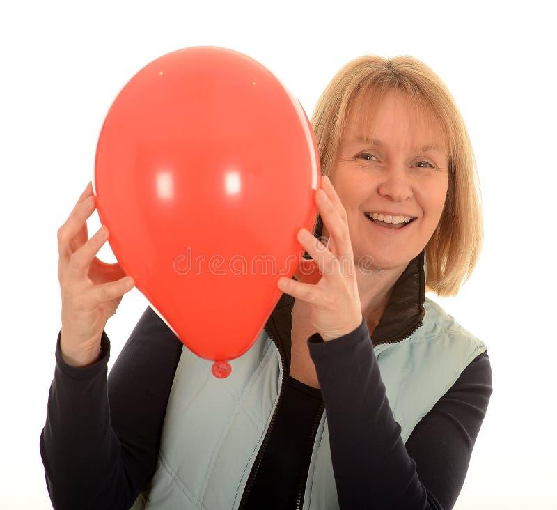 Lycklig kvinna med en ballong fotografering för bildbyråer