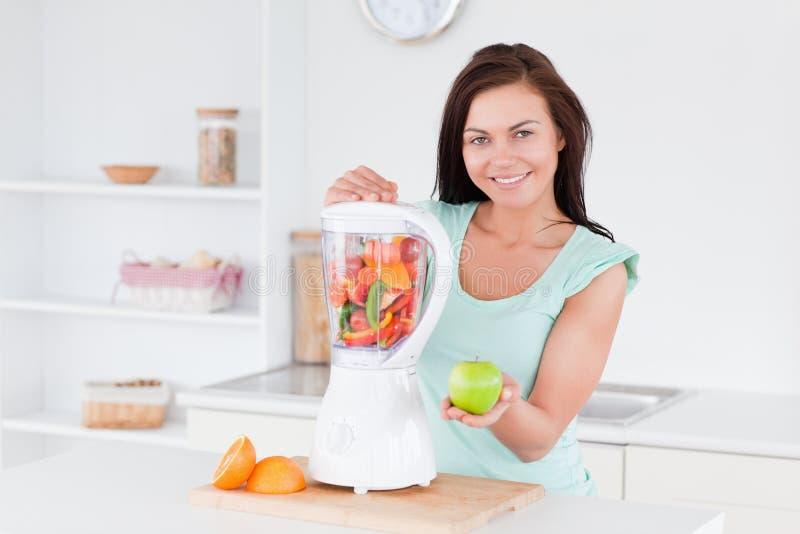 Lycklig kvinna med en blandare och ett äpple fotografering för bildbyråer
