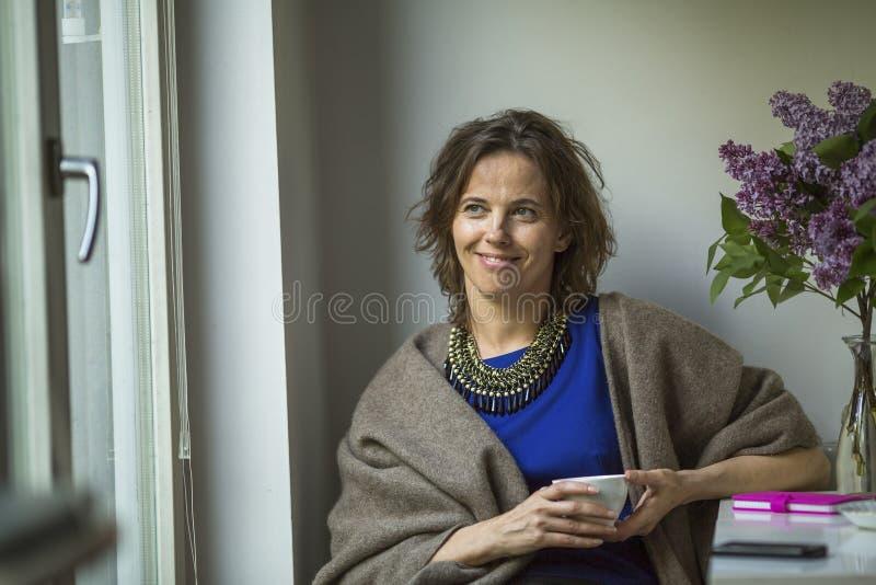 Lycklig kvinna med en kopp te i hand royaltyfria bilder