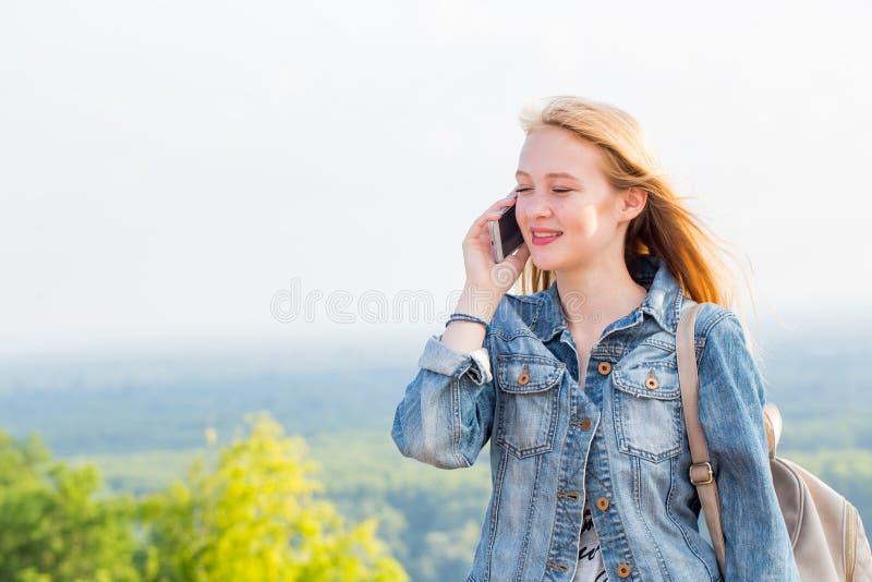 Lycklig kvinna med ett leende som talar på telefonen, medan gå i parkera Livsstil fritid, sommar, teknologi royaltyfri foto