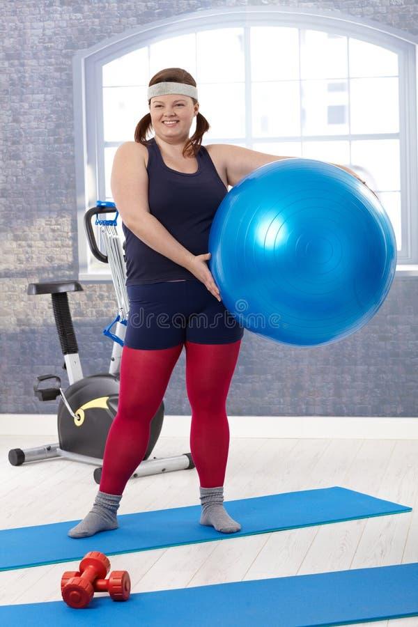 Lycklig kvinna med fitbollen fotografering för bildbyråer