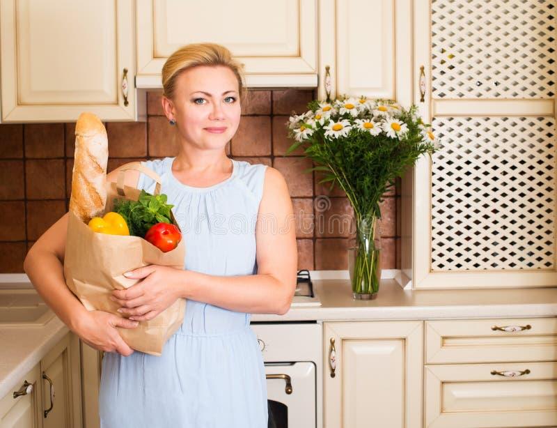 Lycklig kvinna med grönsaker och bröd i pappers- shoppingpåse _ arkivbilder