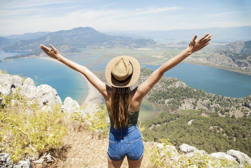 Lycklig kvinna med händer upp att stå på klippan över havet och öar på sommar Tappninglynne, begrepp av vinnaren, frihet, lycka e royaltyfria foton