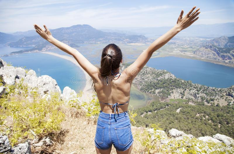 Lycklig kvinna med händer upp att stå på klippan över havet och öar på sommar Tappninglynne, begrepp av vinnaren, frihet, lycka e arkivfoton