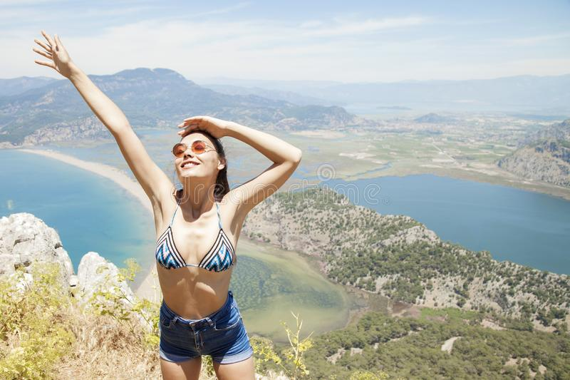 Lycklig kvinna med händer upp att stå på klippan över havet och öar på sommar Tappninglynne, begrepp av vinnaren, frihet, lycka e royaltyfri bild