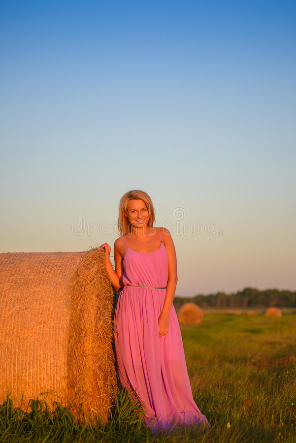 Lycklig kvinna med hö i ängfält arkivbilder