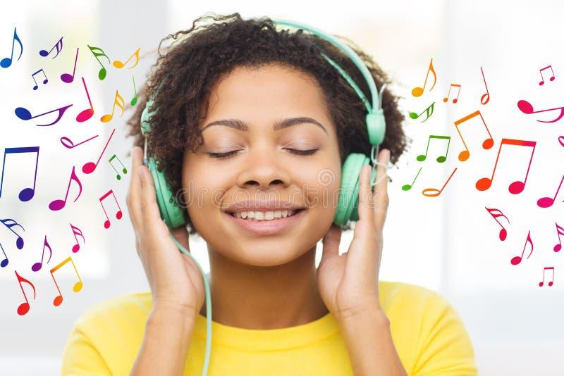 Lycklig kvinna med hörlurar som lyssnar till musik arkivfoton