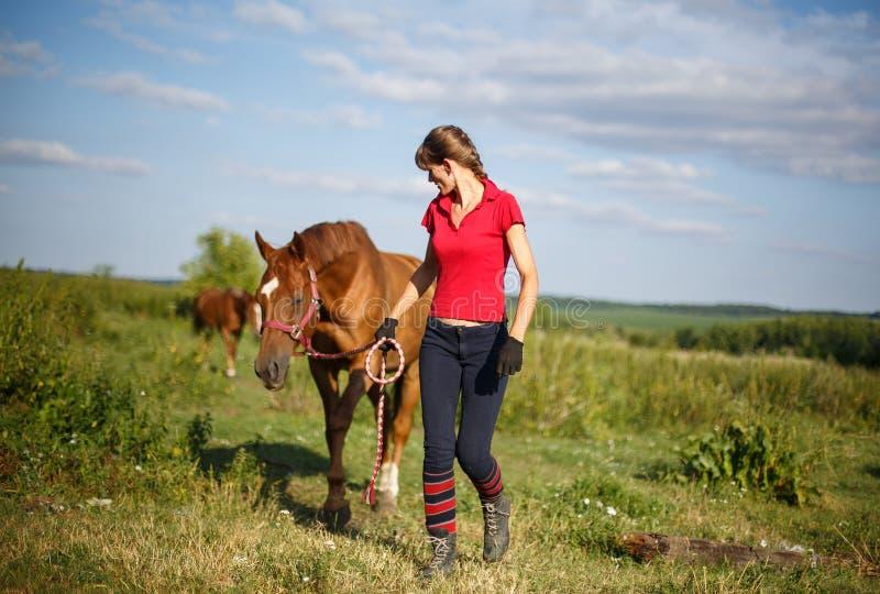 Lycklig kvinna med hennes häst - härlig ung skicklig ryttarinna arkivfoton