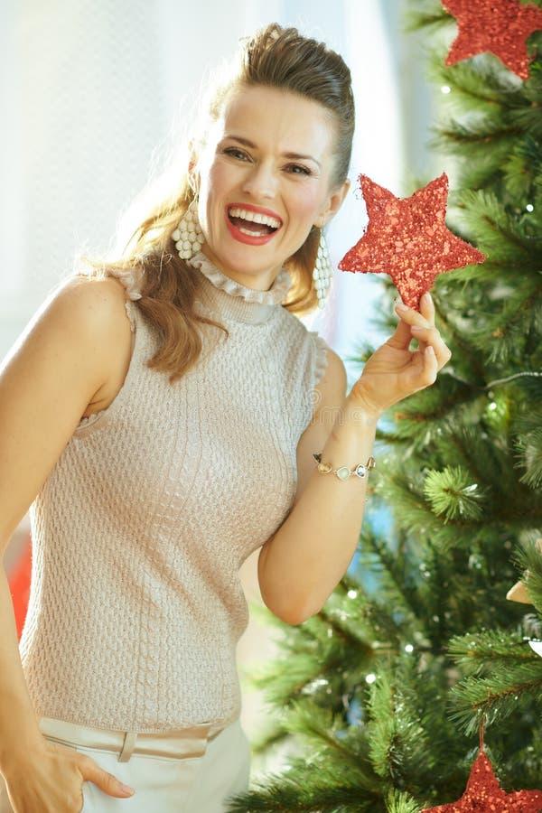 Lycklig kvinna med julstjärnan nära julgranen royaltyfria foton