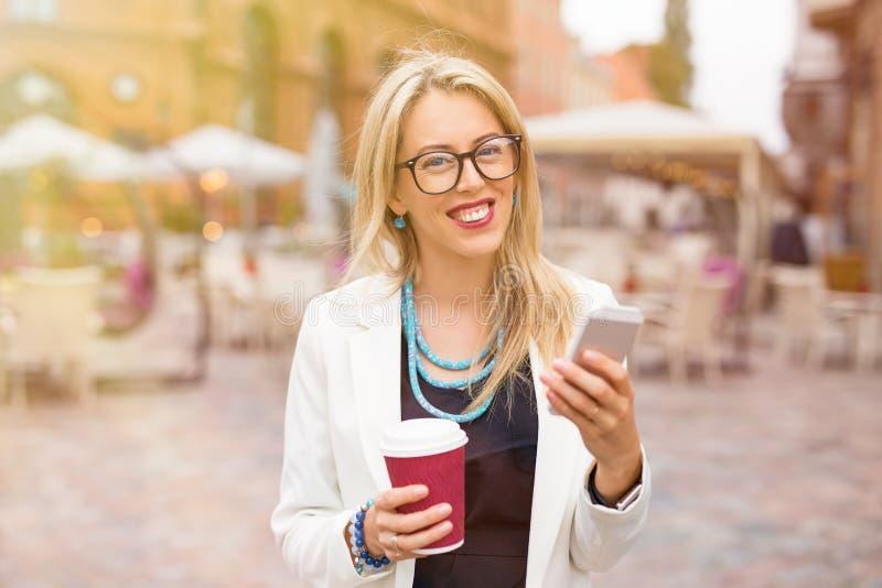 Lycklig kvinna med kaffe och smartphonen i staden royaltyfri fotografi
