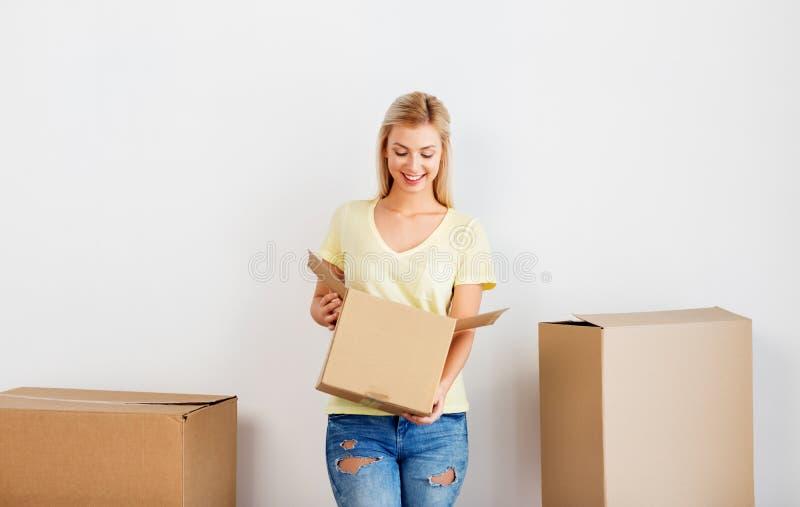 Lycklig kvinna med kartongen som flyttar sig till det nya hemmet arkivfoto