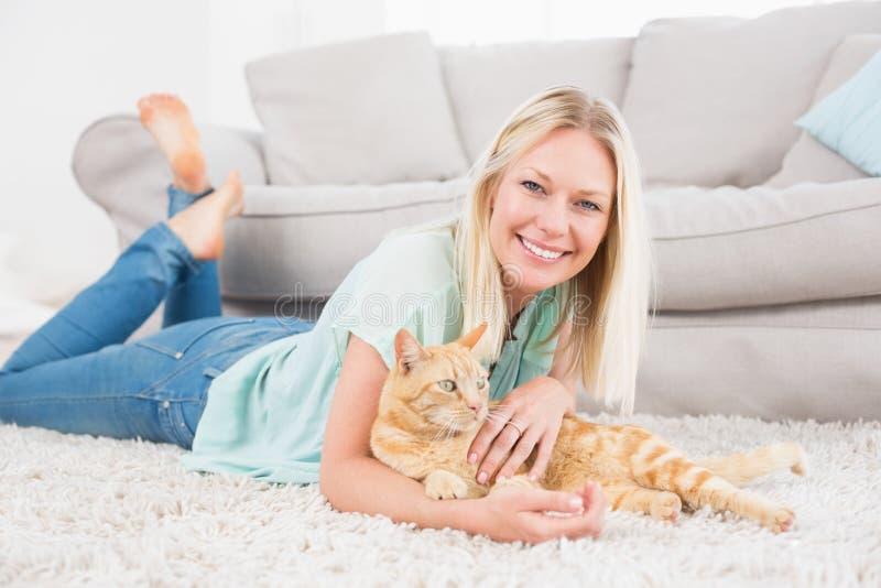 Lycklig kvinna med katten som ligger på filten royaltyfri fotografi