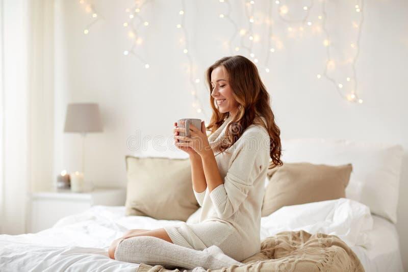 Lycklig kvinna med koppen kaffe i säng hemma royaltyfria foton