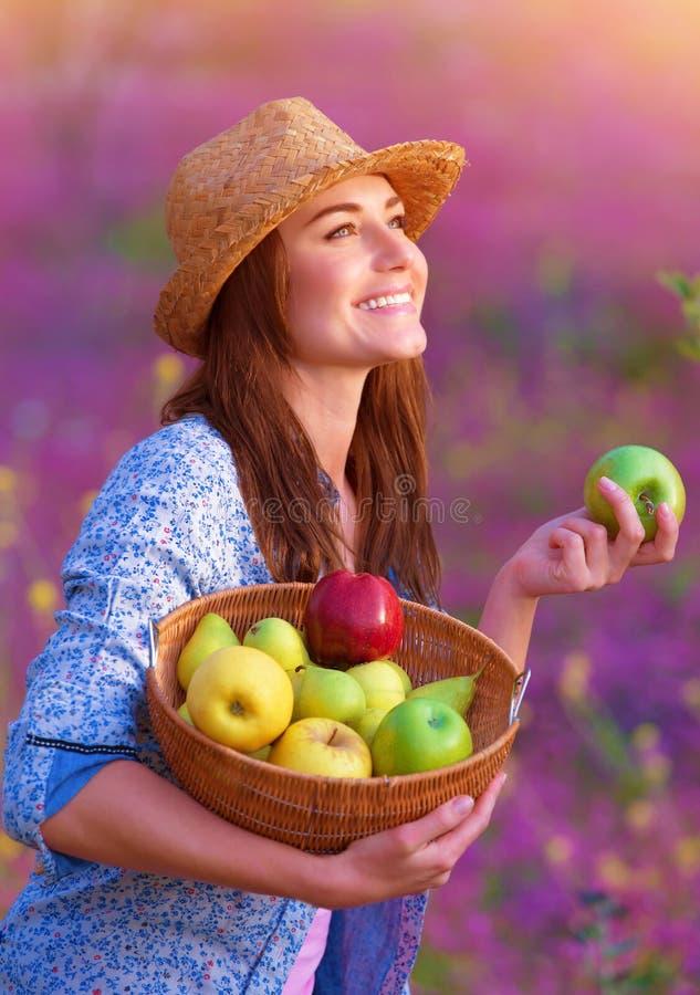 Lycklig kvinna med korgen av äpplen royaltyfria bilder