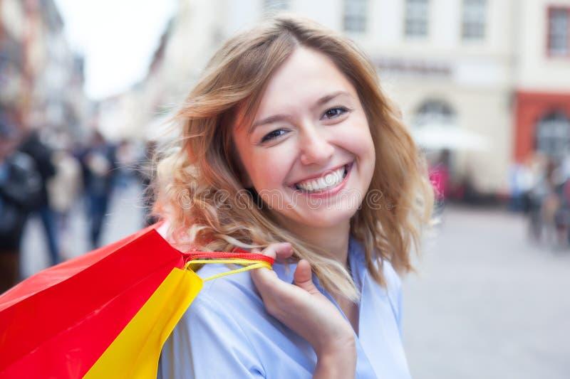 Lycklig kvinna med lockigt blont hår och shoppingpåsar i staden arkivbild