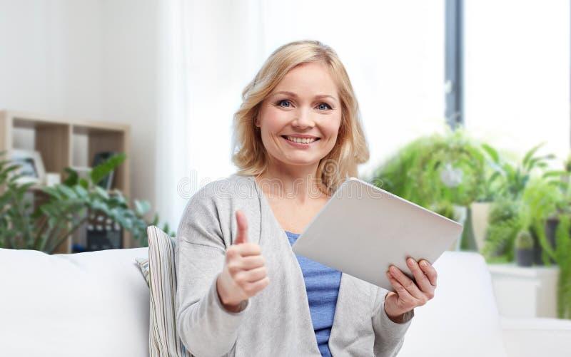 Lycklig kvinna med minnestavlaPC:n som visar upp tummar royaltyfria bilder