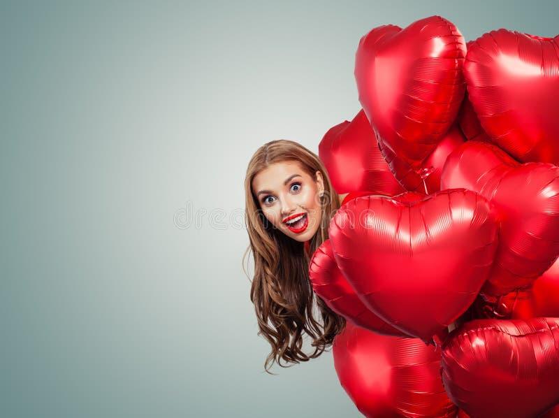 Lycklig kvinna med röd hjärta för ballonger på vit bakgrund med kopieringsutrymme Förvånad flicka med röd kantmakeup på stort ban royaltyfri foto