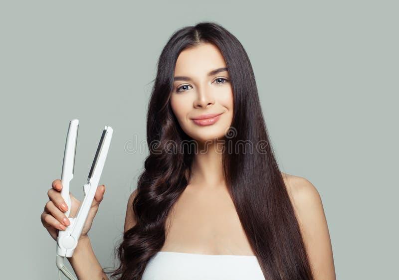 Lycklig kvinna med rakt hår och lockigt hår genom att använda hårstraighteneren Gullig flicka som rätar ut den sunda brunettfrisy fotografering för bildbyråer