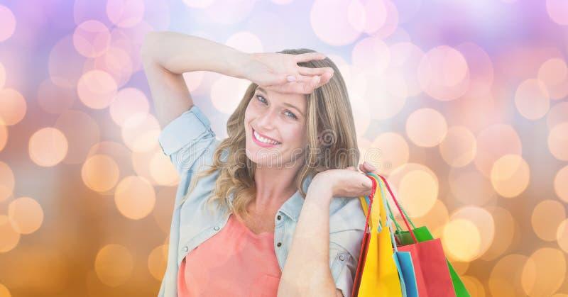 Lycklig kvinna med shoppingpåsar över suddighetsbakgrund royaltyfri bild
