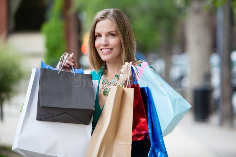 Lycklig kvinna med shoppingpåsar royaltyfria foton