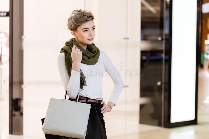 Lycklig kvinna med shoppingpåsar i mitt av den vita suddiga shoppinggallerian arkivfoto