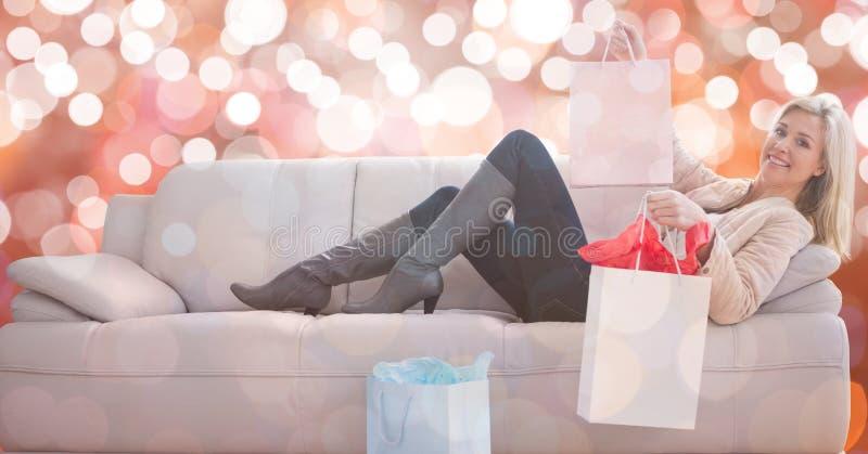 Lycklig kvinna med shoppingpåsar som ligger på soffan över bokeh arkivbild