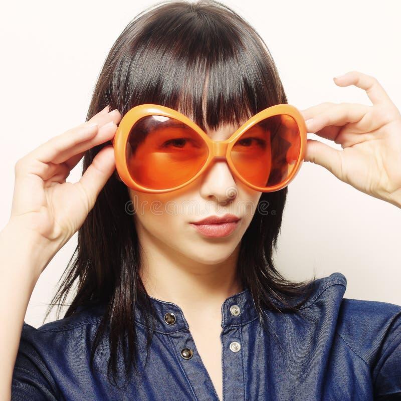 Lycklig kvinna med stor orange solglasögon royaltyfri fotografi