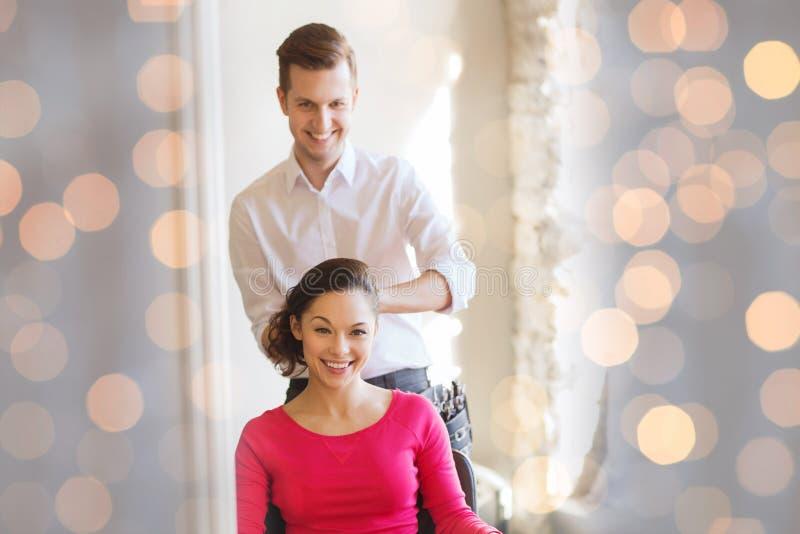 Lycklig kvinna med stylistdanandefrisyren på salongen royaltyfria bilder