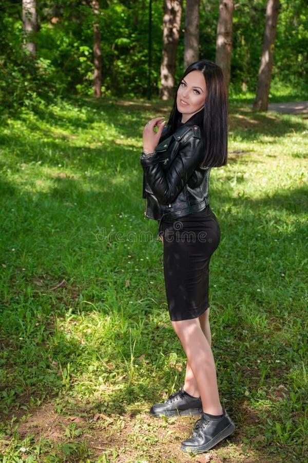 Lycklig kvinna med tandleenden som poserar på gläntan i skogen på en solig vårdag royaltyfri bild