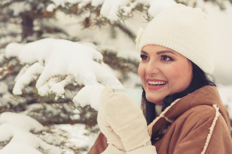 Lycklig kvinna med te- eller kaffekoppen som tycker om vintersolen arkivfoton