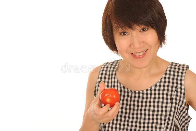 Lycklig kvinna med tomaten royaltyfria foton