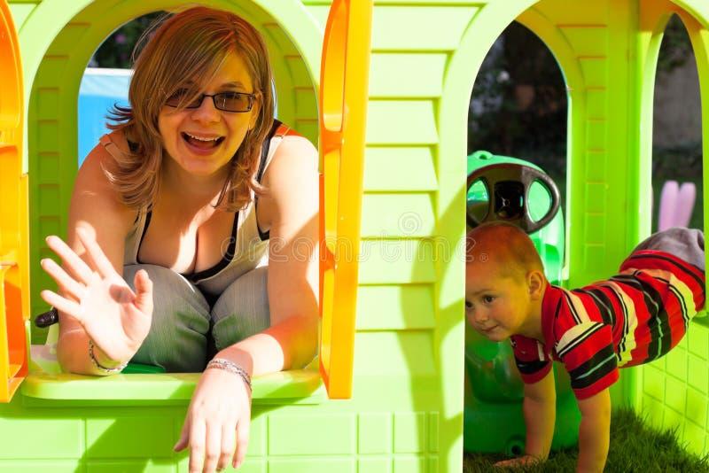 Lycklig kvinna och barn i lekstuga royaltyfri foto