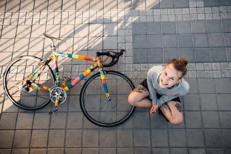 Lycklig kvinna och cykel i staden royaltyfria foton