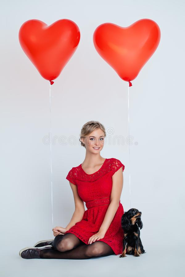 Lycklig kvinna och gullig valphund med röda hjärtaballonger royaltyfri foto