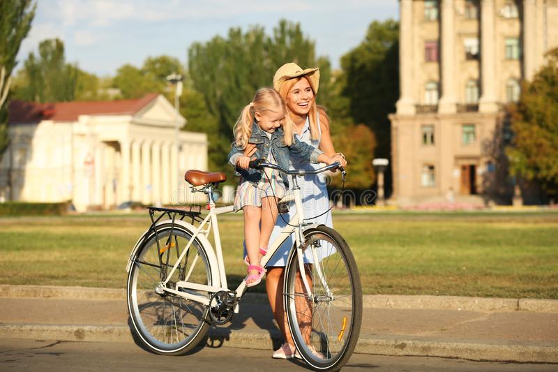 Lycklig kvinna och hennes lilla dotter med cykeln utomhus arkivfoton