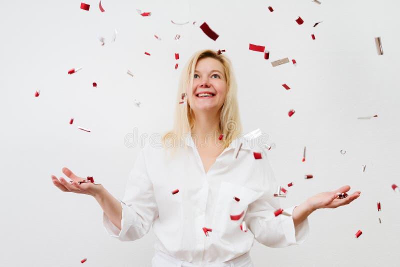 Lycklig kvinna på berömpartiet med fallande everywhe för konfettier arkivbilder