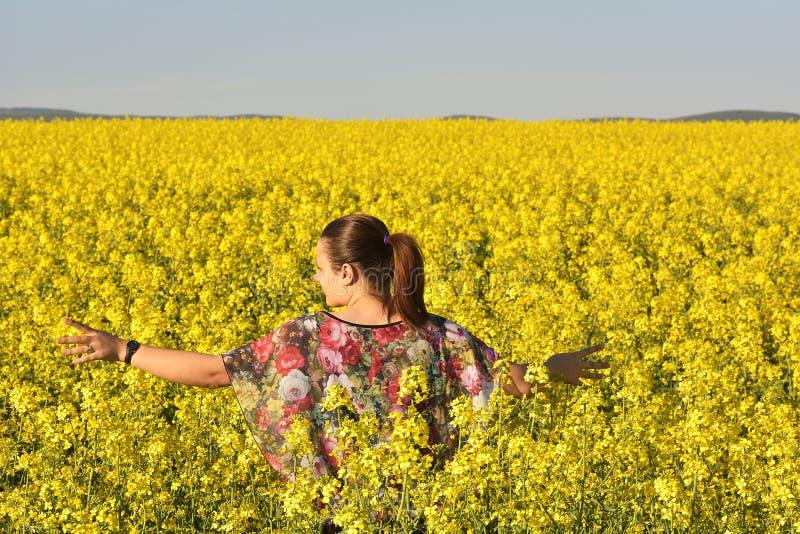 Lycklig kvinna på blommande rapsfröfält i vår royaltyfri foto